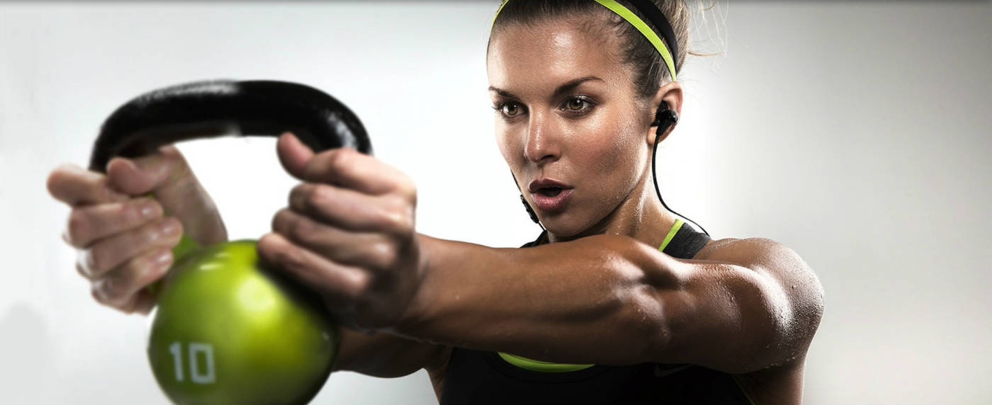 Women holding a kettlebell infront of her muscle soreness