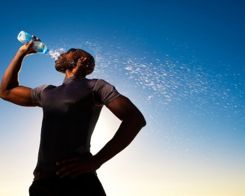 Silhouette of a man drinking water after exercising with blue sky in the background.