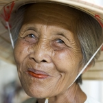 Portrait of an old Asian woman with a Vietnamese hat