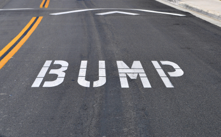 The word bump spelled out on the street before a speed bump, which is also know as a sleeping policeman, kipping cop, slow child, road hump, speed hump, speed breaker, judder bar, or ramp.