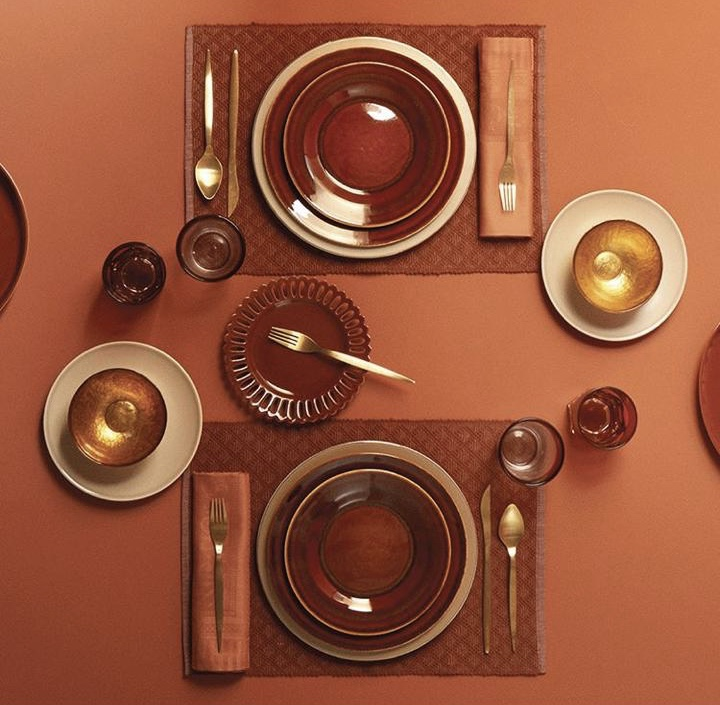 Terracotta colored table, cutlery and plates